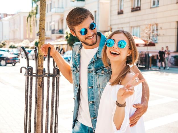Uśmiechnięta piękna dziewczyna i jej przystojny chłopak pozuje na ulicie.
