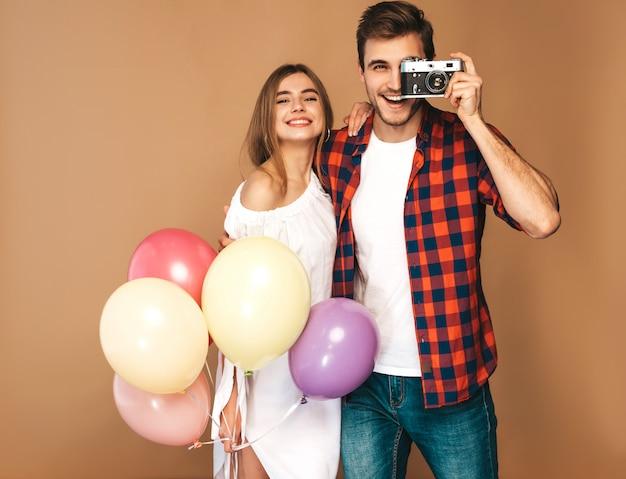 Uśmiechnięta piękna dziewczyna i jej przystojny chłopak trzyma bukiet kolorowych balonów. szczęśliwa para bierze fotografię one na retro kamerze. wszystkiego najlepszego