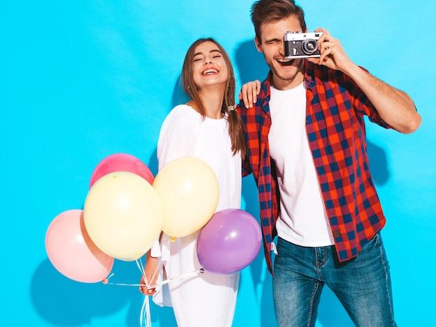 Uśmiechnięta piękna dziewczyna i jej przystojny chłopak trzyma bukiet kolorowych balonów. szczęśliwa para bierze fotografię one. wszystkiego najlepszego