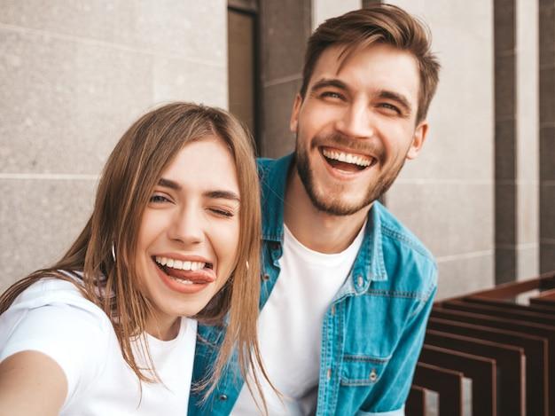 Uśmiechnięta piękna dziewczyna i jej przystojny chłopak w letnie ubrania. szczęśliwa rodzina biorąc selfie autoportret o sobie na aparat w smartfonie. zabawy na ulicy. pokazuje język
