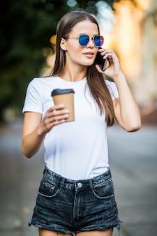 Uśmiechnięta piękna dziewczyna opowiada na telefonie komórkowym i pije kawę na ulicie