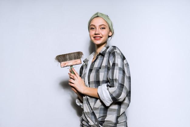 Uśmiechnięta piękna dziewczyna robi naprawy w swoim mieszkaniu, trzymając pędzel do malowania ścian