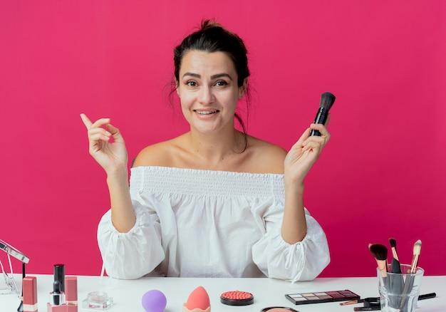 Uśmiechnięta piękna dziewczyna siedzi przy stole z narzędziami do makijażu, trzymając pędzel do makijażu i wskazując na bok na białym tle na różowej ścianie