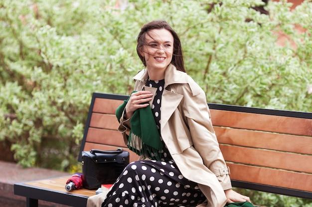Uśmiechnięta piękna dziewczyna siedzi w parku miejskim na ławce. wiatr rozwijający długie włosy szczęśliwej młodej kobiety. skopiuj miejsce
