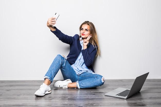 Uśmiechnięta piękna dziewczyna studentka siedzi na podłodze z białą ścianą i rozmowy wideo na telefon komórkowy z happy, gdy ona używa badania komputera przenośnego.