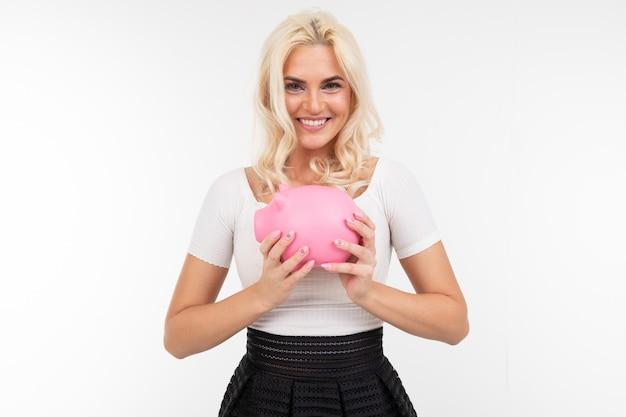Uśmiechnięta piękna dziewczyna w czarny i biały ubraniach z prosiątko bankiem w rękach na białym tle z kopii przestrzenią