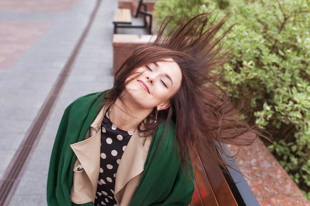Uśmiechnięta piękna dziewczyna w mieście. wiatr rozwijający długie włosy szczęśliwej młodej kobiety. portret ślicznej dziewczyny z zamkniętymi oczami. skopiuj miejsce