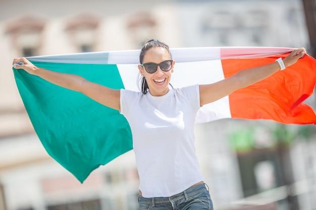 Uśmiechnięta piękna dziewczyna w okularach przeciwsłonecznych i białej koszulce trzyma włoską flagę na ulicy świętuje.