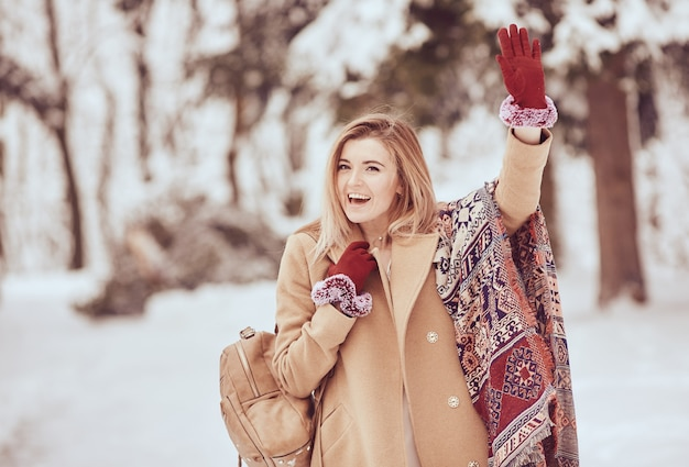 Uśmiechnięta piękna dziewczyna w stylowej zimy perspektywie