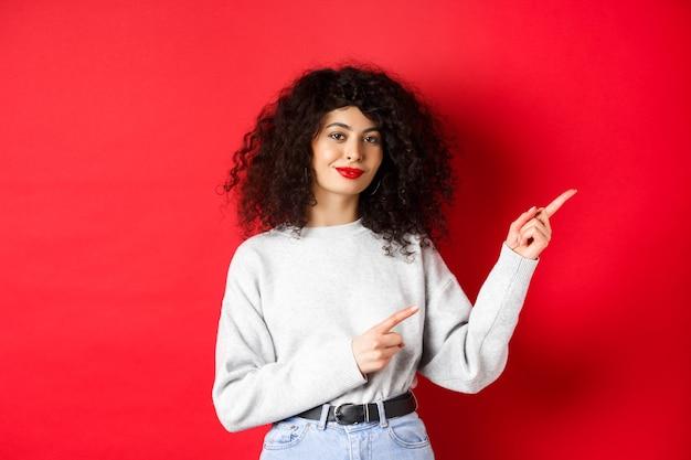 Uśmiechnięta piękna dziewczyna z kręconymi włosami, wskazując palcem w prawo, pokazuje reklamę, czerwona ściana