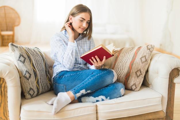Uśmiechnięta piękna kobieta czyta opowieści książkę