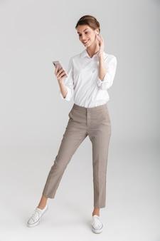 Uśmiechnięta piękna kobieta korzystająca z bezprzewodowej słuchawki i telefonu komórkowego izolowanych na białym tle