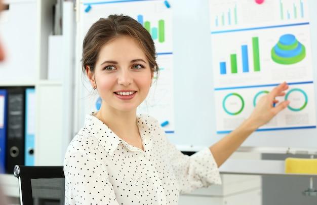 Uśmiechnięta piękna kobieta mówi coś ważnego w biurze