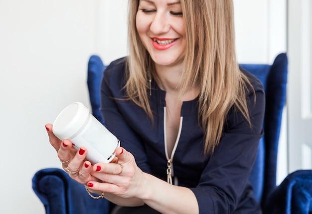 Uśmiechnięta piękna kobieta patrzy na lekarstwo w ręku, używając go dla zdrowia i urody.