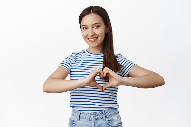 Uśmiechnięta piękna kobieta pokazuje gest serca w pobliżu klatki piersiowej, wyraża sympatię lub sympatię, pasjonuje się czymś, stoi na białej ścianie w koszulce