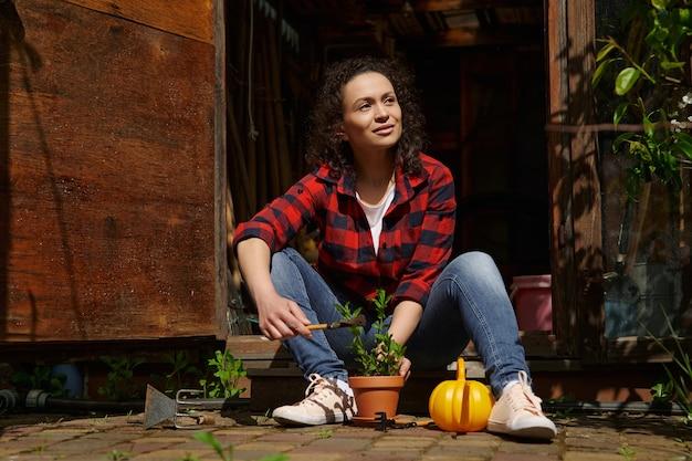 Uśmiechnięta piękna kobieta siedzi na wyciągnięcie ręki w drewnianej altanie wiejskiego domu i cieszy się ogrodnictwem w ciepły słoneczny dzień