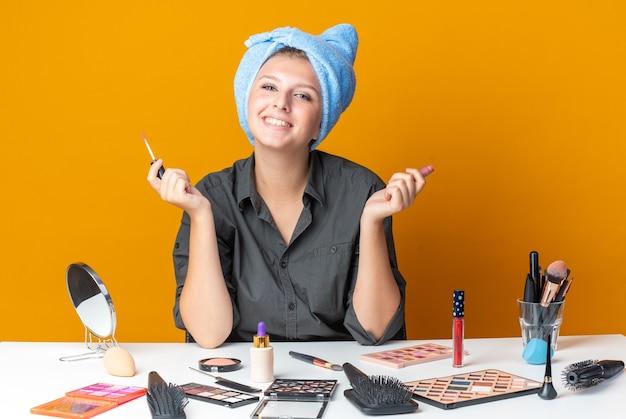 Uśmiechnięta piękna kobieta siedzi przy stole z narzędziami do makijażu owiniętymi włosami w ręcznik, trzymając błyszczyk