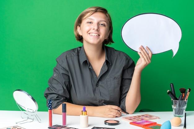 Uśmiechnięta piękna kobieta siedzi przy stole z narzędziami do makijażu, trzymając dymek z pędzelkiem do makijażu
