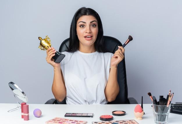 Uśmiechnięta piękna kobieta siedzi przy stole z narzędziami do makijażu, trzymając kubek zwycięzcy za pomocą pędzla do pudru