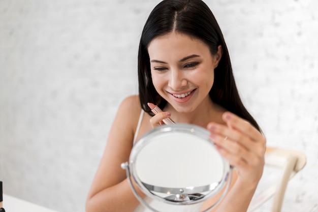 Uśmiechnięta piękna kobieta świeża zdrowa skóra patrzeje na lustrze i stosuje pomadkę