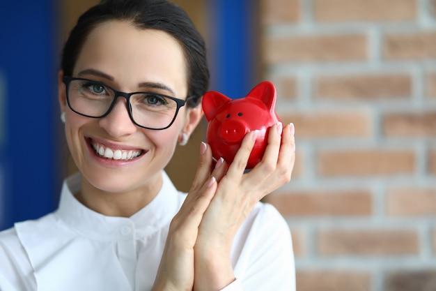 Uśmiechnięta piękna kobieta trzyma prosiątko prosiątka banka