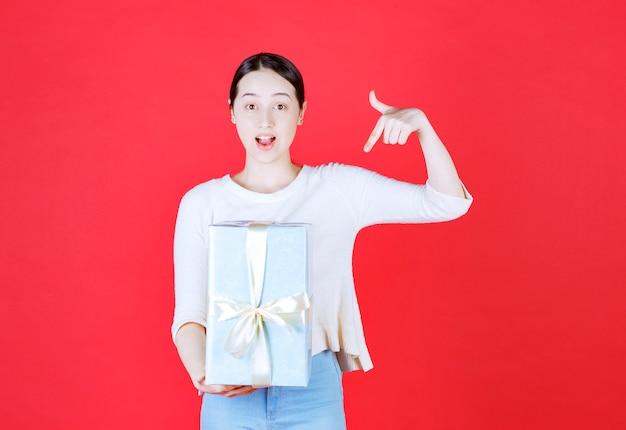 Uśmiechnięta piękna kobieta trzyma pudełko i wskazuje na nim palec