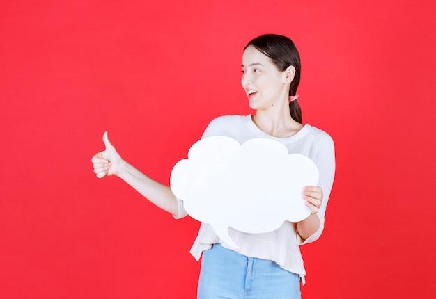 Uśmiechnięta piękna kobieta trzymająca dymek i wskazująca kciukiem w górę