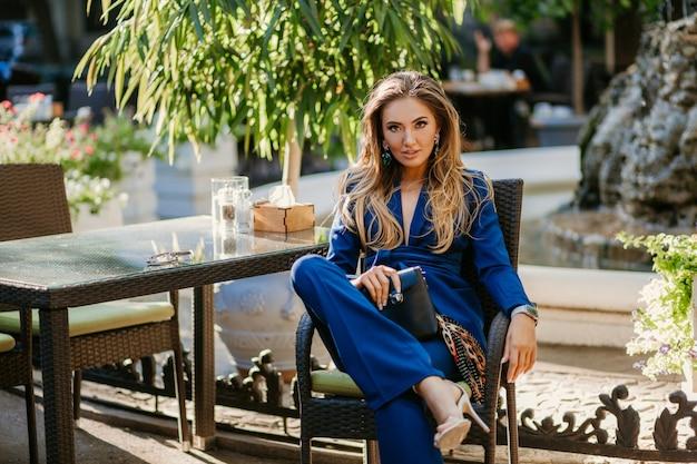 Uśmiechnięta piękna kobieta ubrana w elegancki niebieski garnitur siedzi w kawiarni w słoneczny jesienny dzień