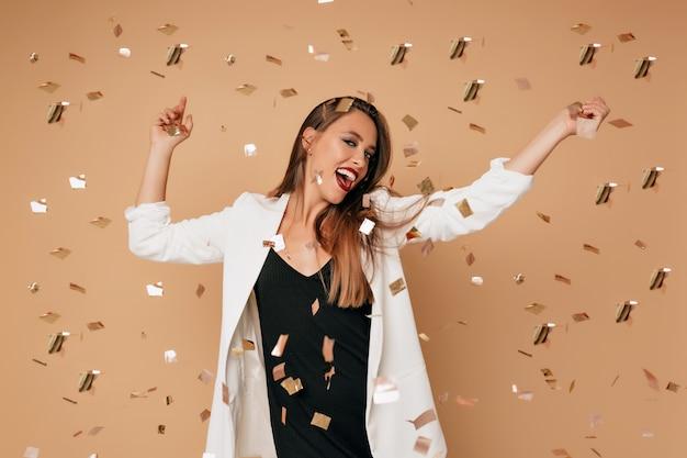 Uśmiechnięta piękna kobieta ubrana w ubranie z ustami winorośli, pozowanie na beżowej ścianie, odwracając wzrok i tańcząc z konfetti
