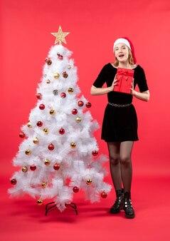 Uśmiechnięta piękna kobieta w czarnej sukni i kapeluszu świętego mikołaja stojącego w pobliżu białego nowego roku drzewa i trzymając prezent na czerwono