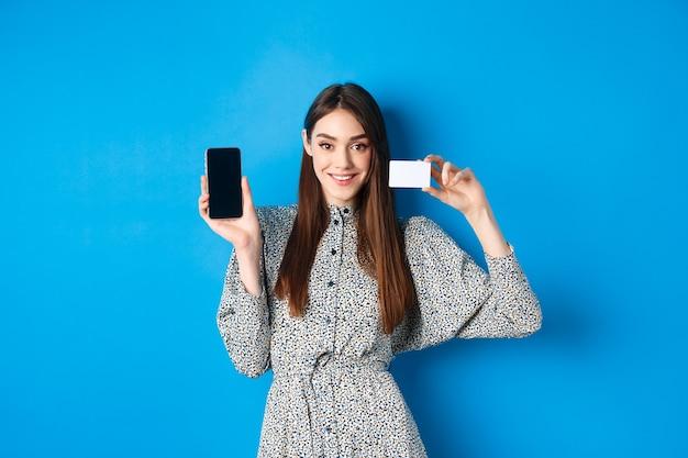 Uśmiechnięta piękna kobieta w sukience pokazująca plastikową kartę kredytową i smartfon