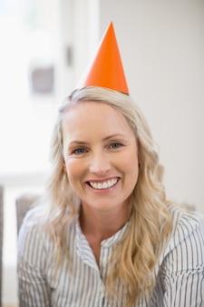 Uśmiechnięta piękna kobieta z partyjnym kapeluszem