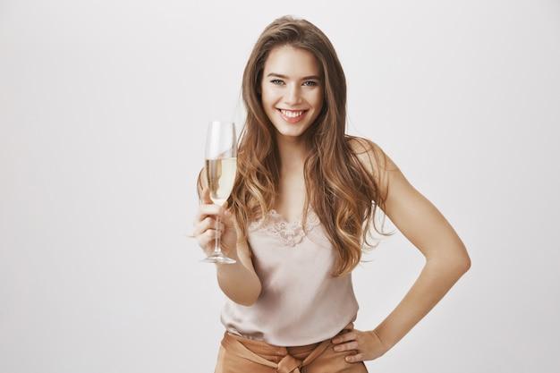 Uśmiechnięta piękna kobieta z szklanym szampanem