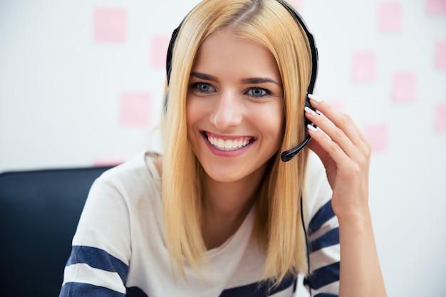 Uśmiechnięta piękna kobieta z zestawem słuchawkowym