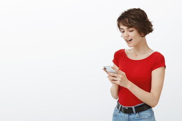 Uśmiechnięta piękna kobieta za pomocą aplikacji na telefon komórkowy, przeczytaj wiadomość z zadowoloną twarzą