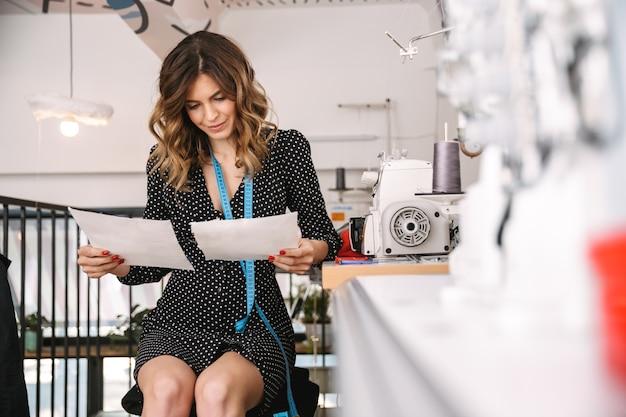 Uśmiechnięta piękna krawcowa kobieta pracuje w warsztacie, wybierając materiały