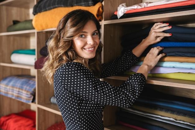 Uśmiechnięta piękna krawcowa kobieta pracuje w warsztacie