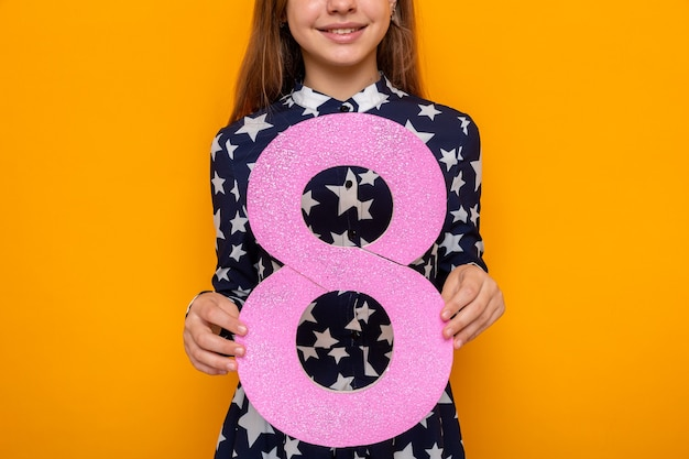 Uśmiechnięta piękna mała dziewczynka w szczęśliwy dzień kobiet trzymająca numer osiem w aparacie odizolowana na pomarańczowej ścianie