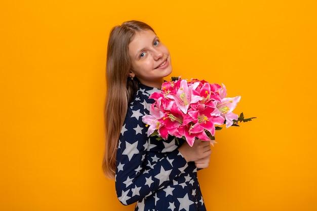 Uśmiechnięta piękna mała dziewczynka w szczęśliwy dzień kobiety trzymająca bukiet odizolowany na pomarańczowej ścianie