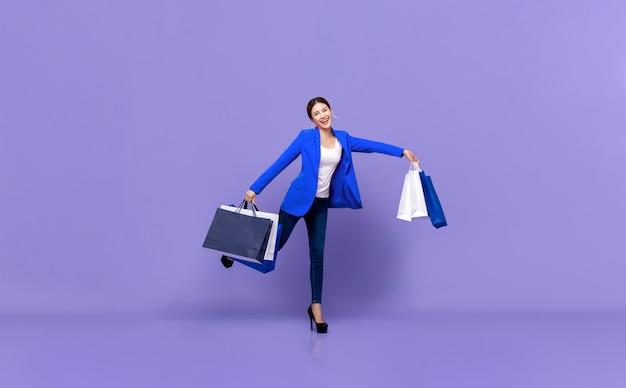 Uśmiechnięta piękna młoda azjatycka kobieta trzyma torby na zakupy