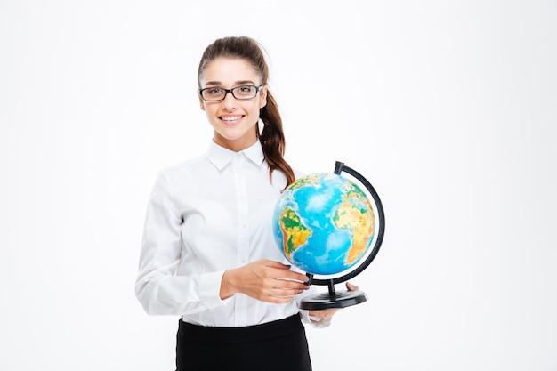 Uśmiechnięta piękna młoda bizneswoman w okularach stojąca i trzymająca kulę ziemską nad białą ścianą