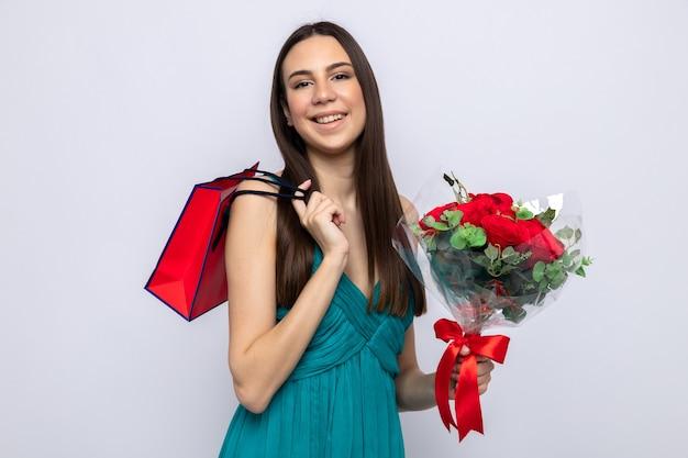 Uśmiechnięta piękna młoda dziewczyna na szczęśliwy dzień kobiet trzymająca bukiet, kładąc torbę z prezentami na ramieniu na białym tle na białej ścianie