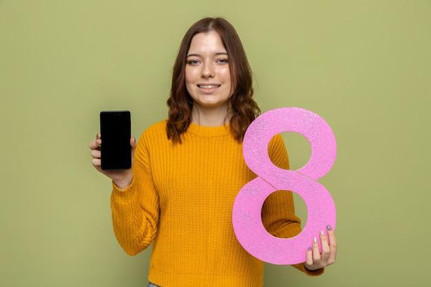 Uśmiechnięta piękna młoda dziewczyna na szczęśliwy dzień kobiet trzymająca numer osiem z telefonem