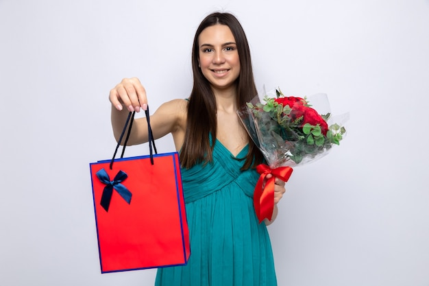 Uśmiechnięta piękna młoda dziewczyna na szczęśliwych walentynkach trzyma bukiet z torbą na prezent
