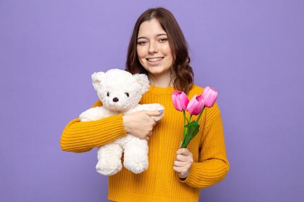 Uśmiechnięta piękna młoda dziewczyna trzyma kwiaty z misiem odizolowanym na niebieskiej ścianie