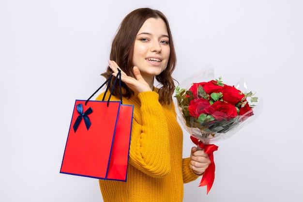 Uśmiechnięta piękna młoda dziewczyna trzyma torbę na prezent z bukietem
