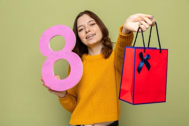 Uśmiechnięta piękna młoda dziewczyna w szczęśliwy dzień kobiet trzymająca numer osiem z torbą na prezent