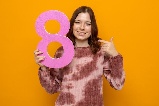 Uśmiechnięta piękna młoda dziewczyna w szczęśliwy dzień kobiety trzyma i wskazuje na numer osiem na pomarańczowej ścianie