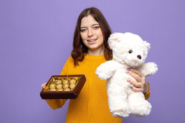 Uśmiechnięta piękna młoda dziewczyna w szczęśliwy dzień kobiety trzymająca misia z pudełkiem cukierków odizolowanych na niebieskiej ścianie