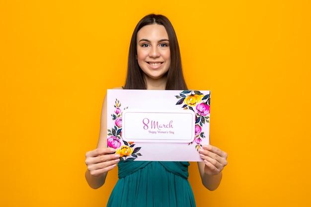 Uśmiechnięta piękna młoda dziewczyna w szczęśliwy dzień kobiety trzymająca pocztówkę odizolowaną na pomarańczowej ścianie